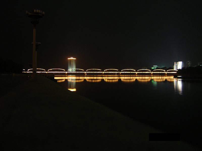 Design moderne: l'illumination nocturne du pont Taedong à travers la rivière Taedong. Pyongyang, Corée du Nord